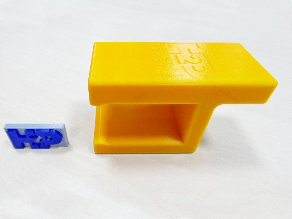 3D tištěná zarážka z PLA (vpravo) zabraňuje pádu dílů na válečkové trati