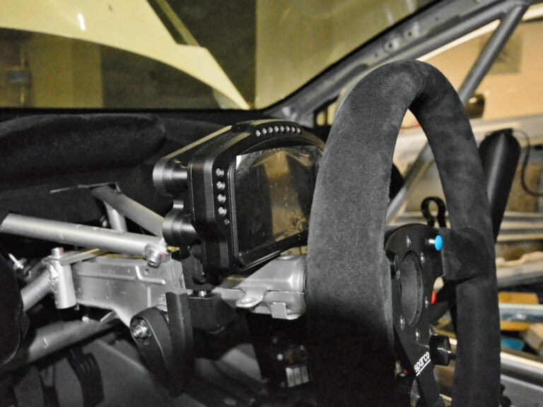 Jizerskohorská strojírna: O bezpečné uchycení kontrolního displeje Cosworth Omega závodního vozu se stará výtisk z kompozitního materiálu Onyx s karbonem připravený na 3D tiskárně Markforged Mark Two. Vytištěn byl i držák řídicí jednotky Cosworth SQ6M a madlo řadící páky s integrovaným senzorem řazení Bosch GSS-2